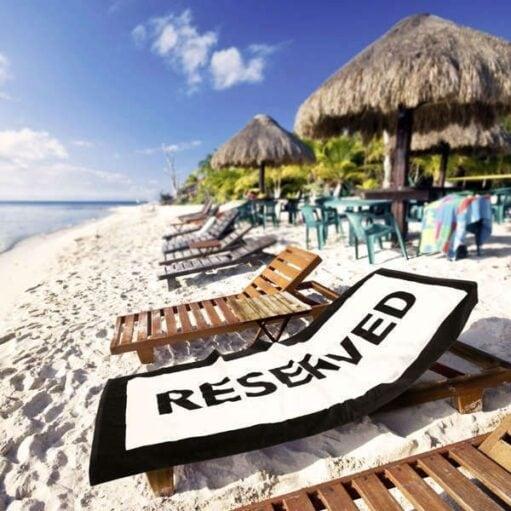 De Reserved Badhanddoek liggend op een strandstoel